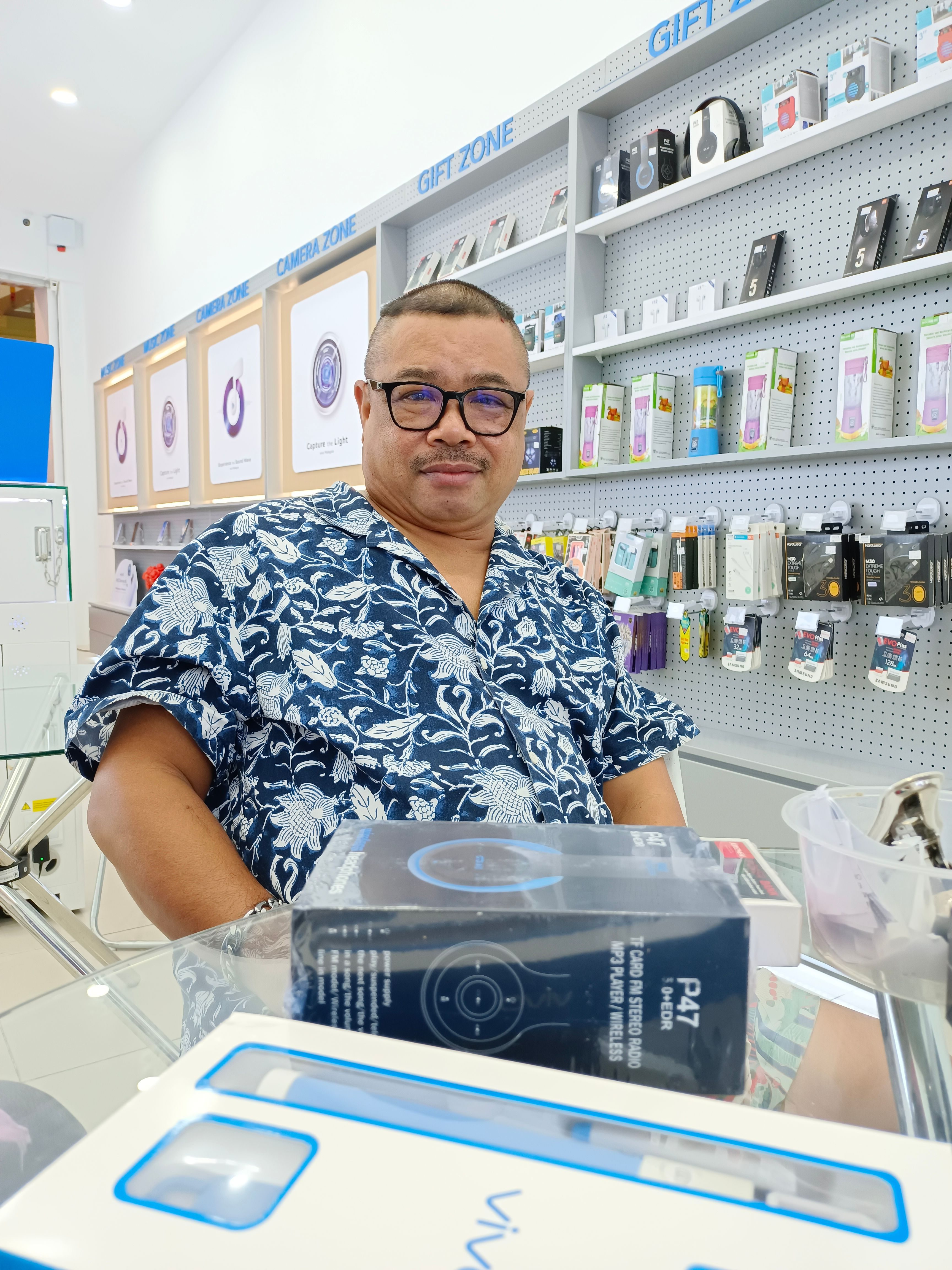 Alias Abdul Hamid poses in an electronic store. He has dark rimmed glasses, short hair and is wearing a floral short sleeved shirt.
