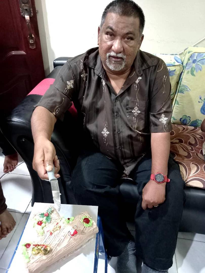 Alyak Sandar memakai baju kemeja bercorak, duduk di atas sofa sambil memotong kek hari lahirnya yang ke-55