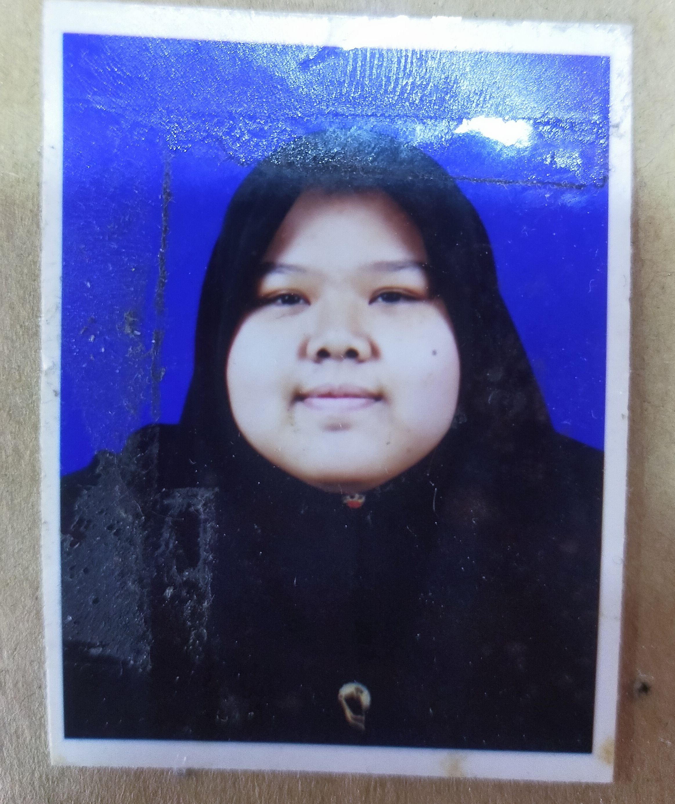 Nur Faten Hanieza MI in a passport photo. She is wearing a black headscarf and is smiling slightly.