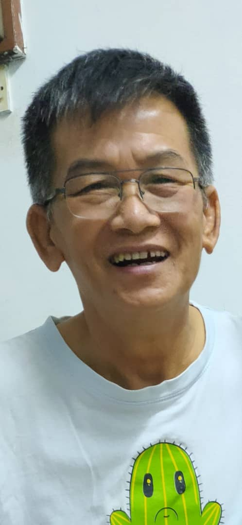 Ho San smiles widely. He has greying thick hair and wears wide rimmed glasses.