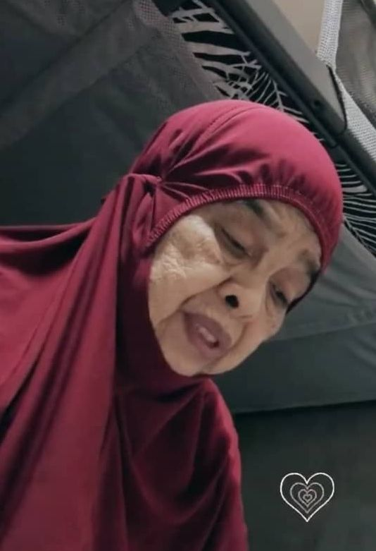 A picture of Merini donning a red telekung for her prayer session