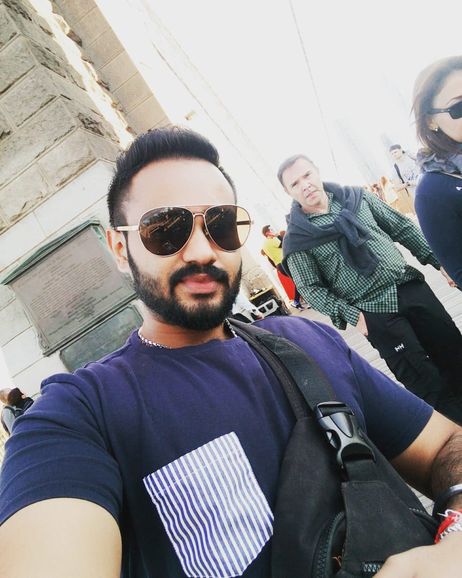 Thinesh Prasadrao, 29, has dark short hair, handlebar mustache and a beard. He is wearing sunglasses and a blue T-shirt. He is taking a selfie.