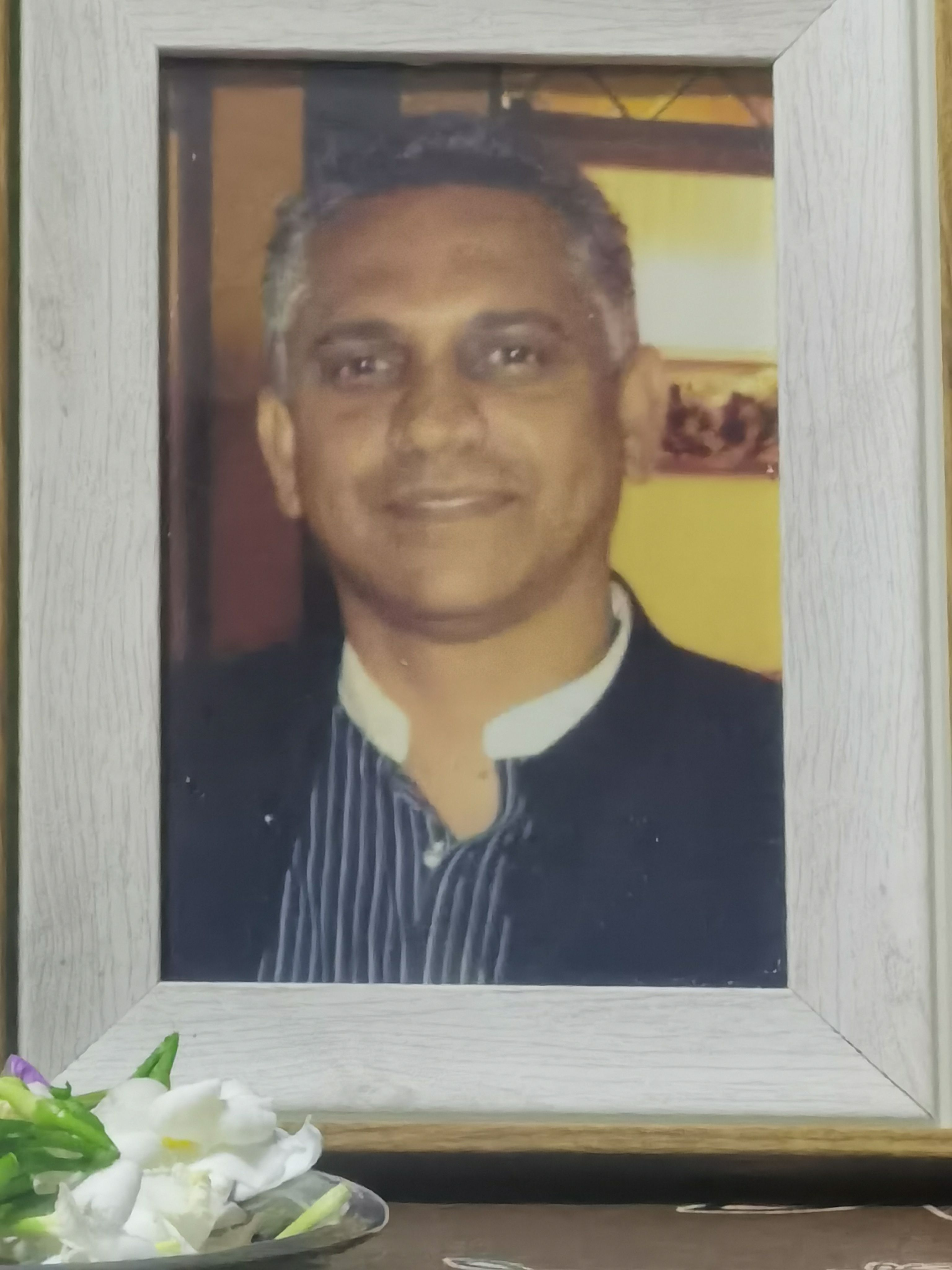A framed picture of P Pramedasa Peeris. He is smiling, and has a dimple. He has short grey hair and a youthful face.