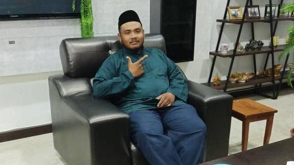 Muhamad Fauzan Bin Saikan sits on a sofa. He gestures to the camera. He is wearing a songkok and baju melayu.