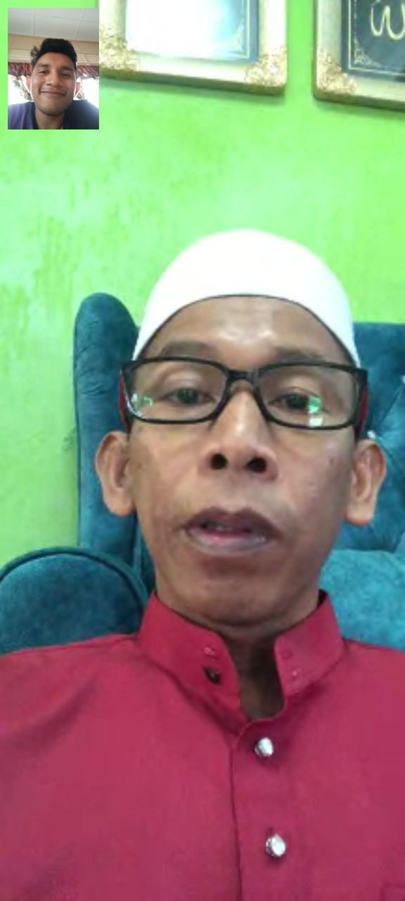 A screenshot of Ahmad Sapali Jamaludin during a video call. He wears a kopiah, dark rimmed glasses and baju melayu.