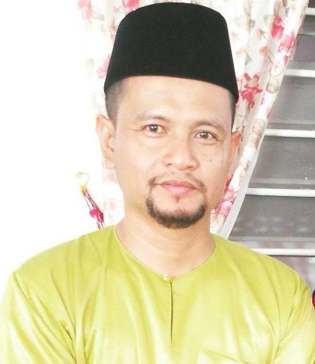 Hazard poses with a smile in a yellow Baju Melayu and black songkok