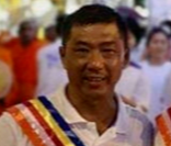 Foo Heng Liang is smiling. He is wearing a white collared T-shirt and a striped sash.