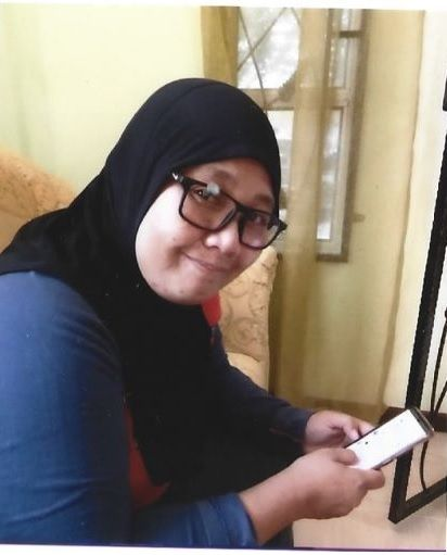 Zuraini Ishak smiles for the camera. She holds a mobile phone and is wearing dark rimmed glasses and a dark headscarf.