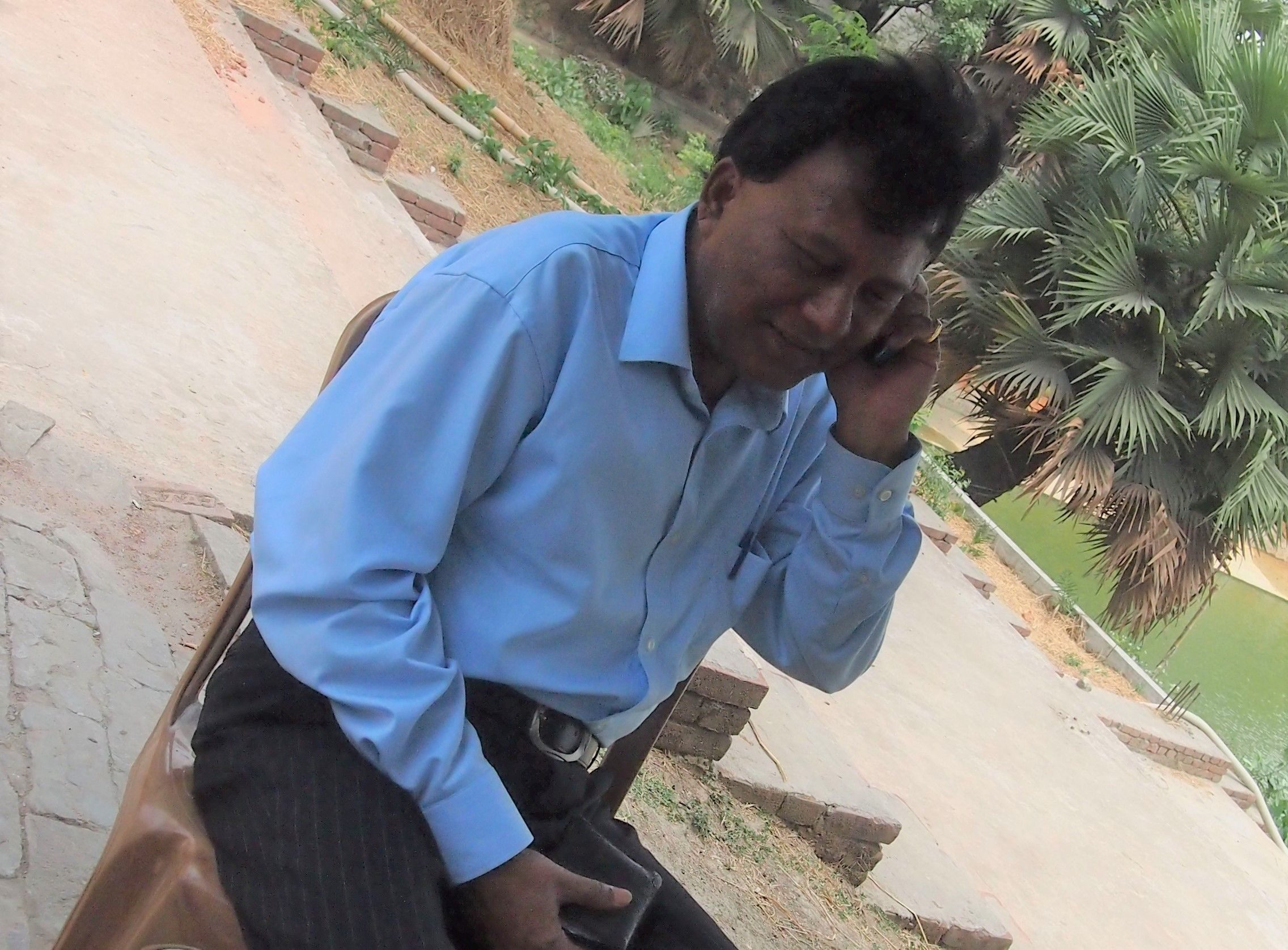 MD Anisuzzaman speaks on the telephone in a park. He is wearing a long sleeved cotton shirt tucked into pinstriped pants. He has thick hair.