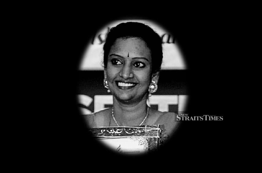 R Kumutha is a woman with brown skin and large eyes. She is pictured smiling, while wearing earrings, a necklace and a pottu on her forehead.