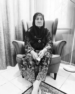 Rokiah Laton sits on a wing chair, while wearing a floral baju kurung and headscarf. The picture was taken on Hari Raya Aidilfitri 2021.