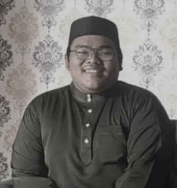 Muhammad Syamim Syazwan Bin Idham in a black kopiah and baju melayu. He is smiling. The picture was taken during Hari Raya Aidilfitri 2021.