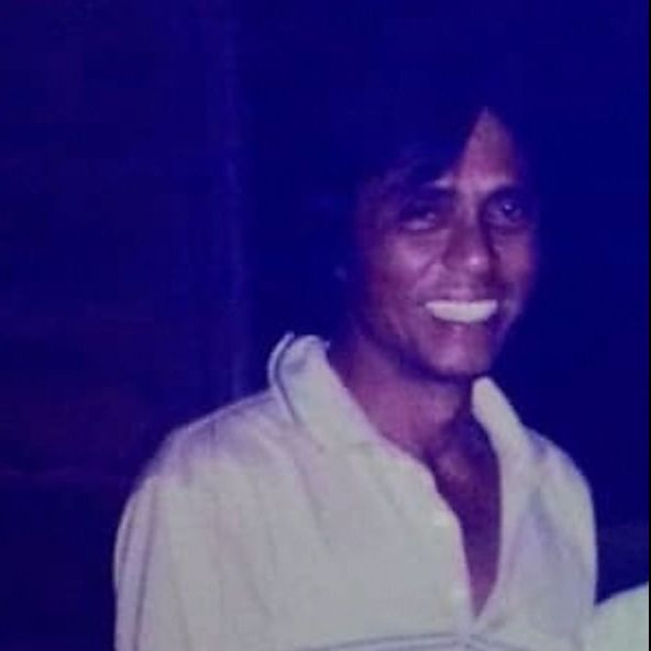 Habib Ahmad bin Habib Zain, 71, has brown skin and floppy black hair. He is wearing a white collared T-shirt with stripes, and a large smile showing teeth.