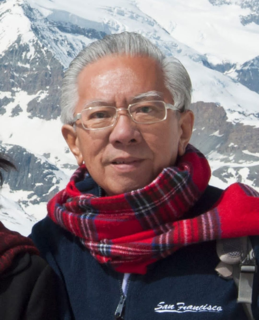 Tan Tho Kim @ Tan Toh Ming posing in front of snow capped mountains in Europe. He has thick white hair and bushy white eyebrows, behind rectangle-framed glasses. He is wearing a red gingham scarf.