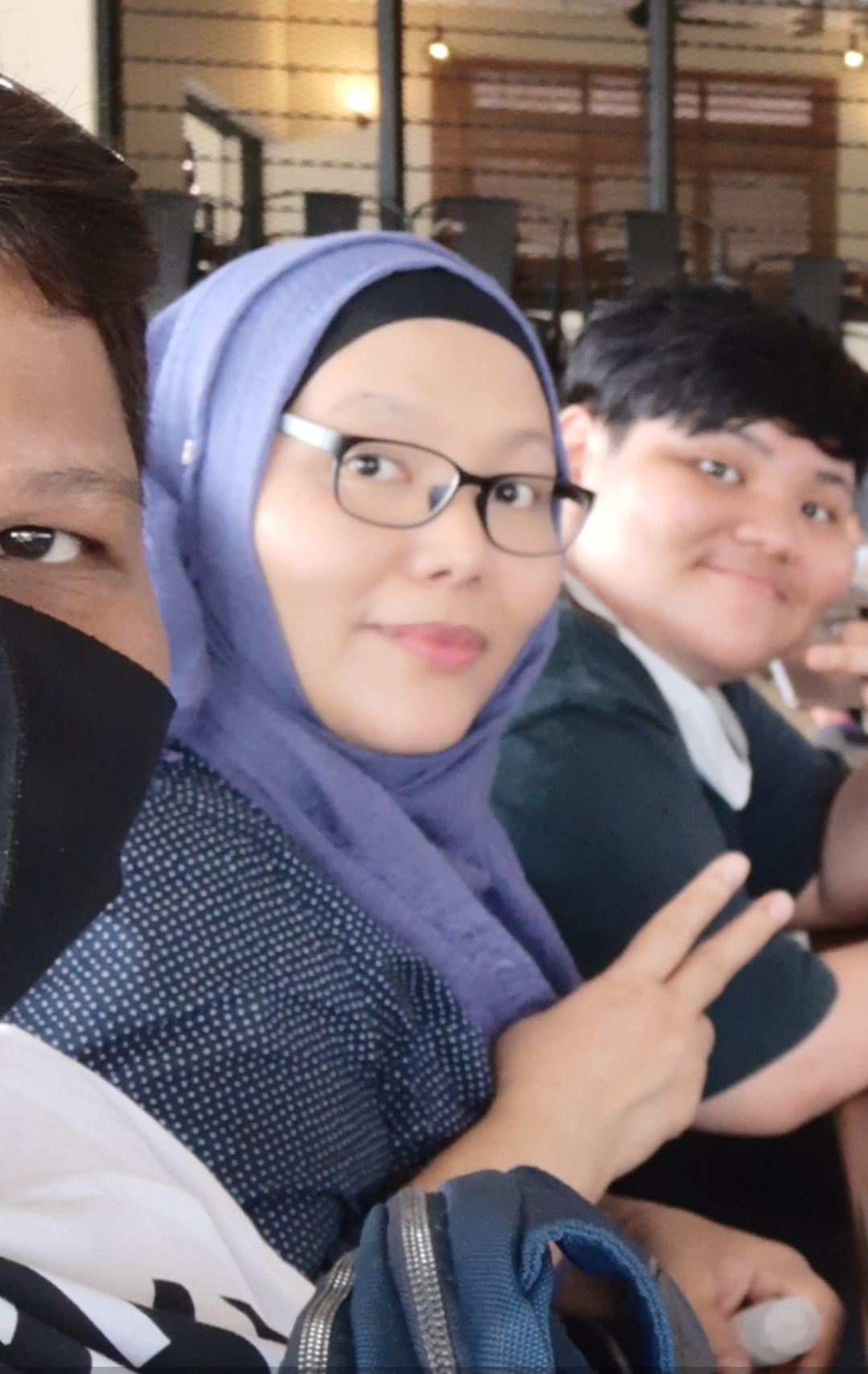 Kamsiah Malik shows the peace sign. She wears a headscarf, polka dot top and dark rimmed glasses.