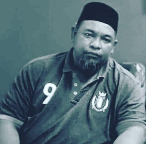 Mohd Hailmi Bin Mohd Shariff wears a songkok and a collared T-shirt with the number 9 printed on the chest. He has a greying goatee.