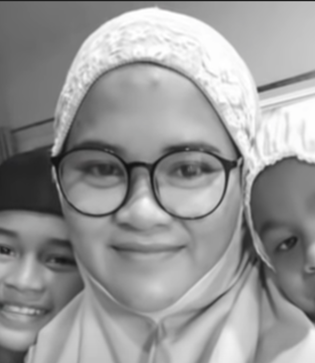 Noriezszah Ishak smiles in a telekung, with two of her young chidren. She has a round face and wears dark rimmed glasses.