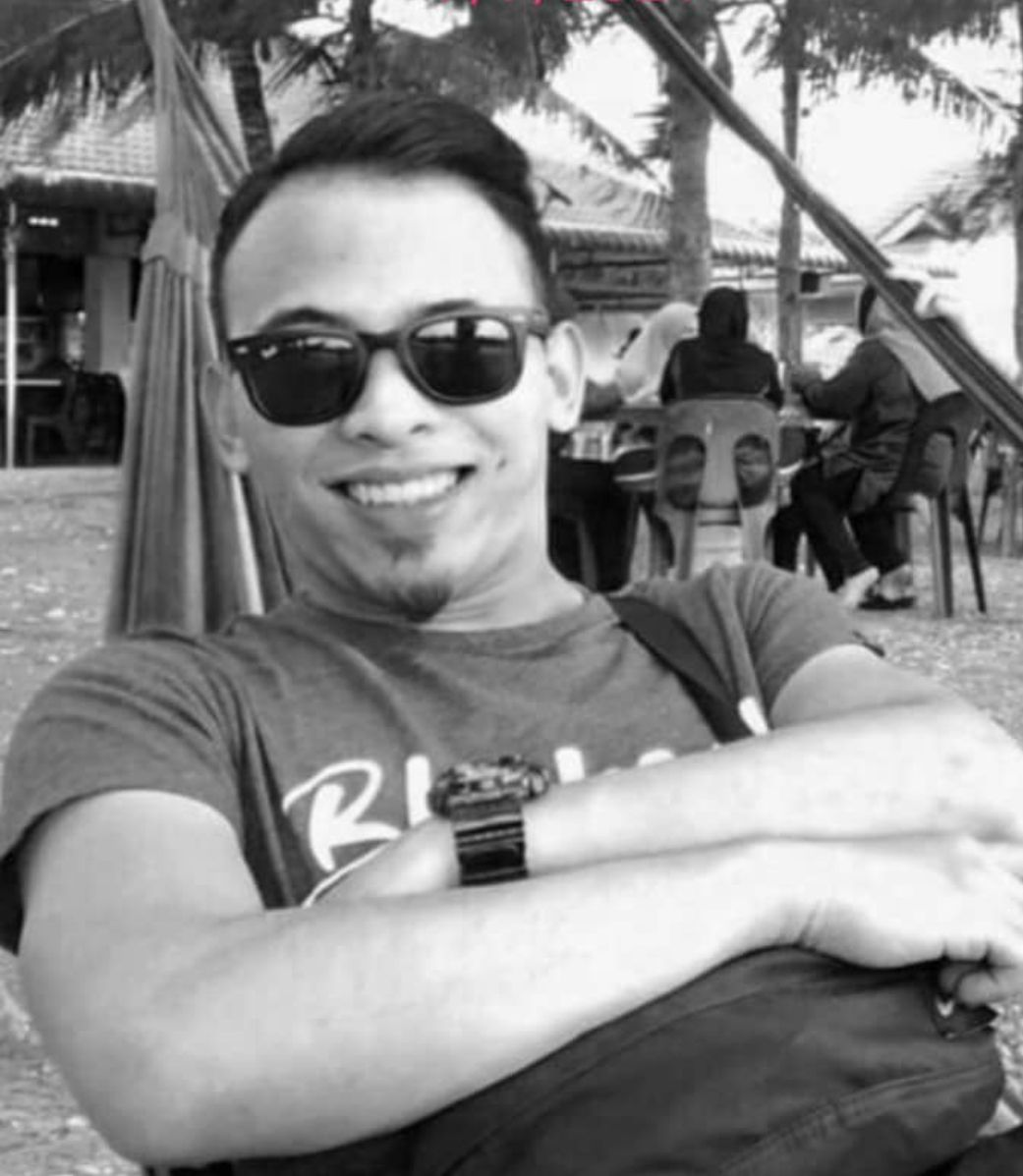 Nor Isna Shukri is a young man. He has a dimple when he smiles, a goatee and side swept hair. He is wearing sunglasse.