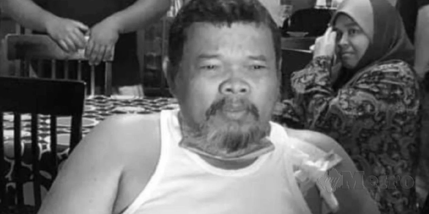 Rodzi Tahar in foreground is rotund, wears a single and has a greying beard. He has an IV port on his shoulder. His wife is in the backrgound in a headscarf and baju kurung.