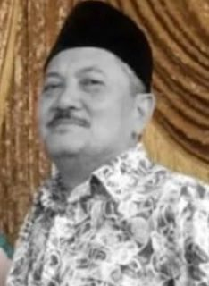 Ismail Putih. Elderly man with mustache, wearing a songkok and patterned collared shirt.