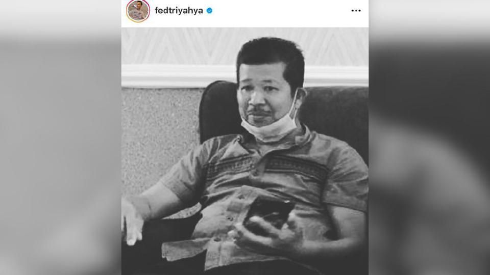 A screenshot of Fedtri Yahya's Instagram post, showing his brother Zahari Othman sitting down with his face mask lowered to his chin. Zahari was holding his phone.