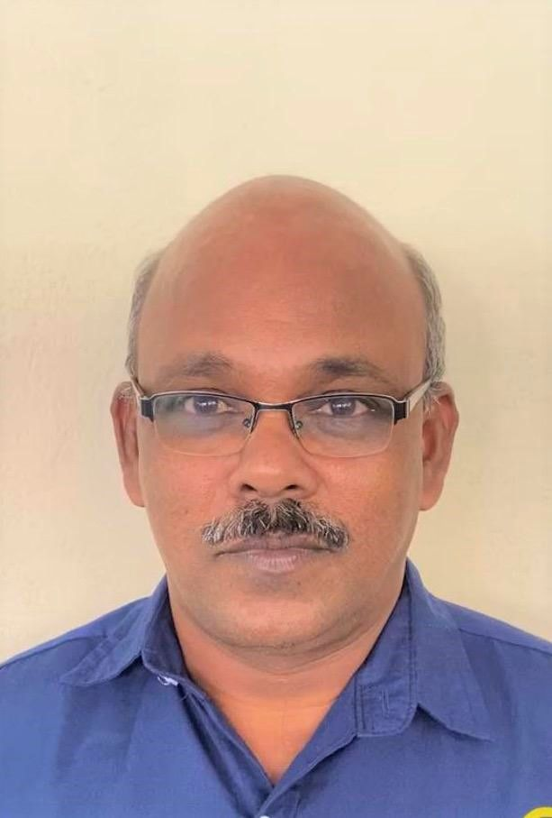 Selvarajan Muthan's passport photo. He is balding, with salt and pepper mustache and spectacles.