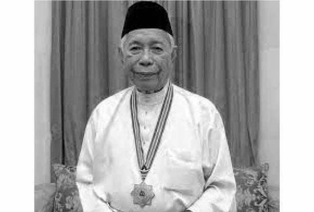 Sakaran wearing baju Melayu and songkok photographed with a medal honoring him as Tokoh Maal Hijrah Nasional.