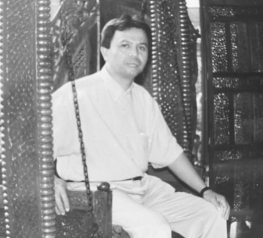 Amarullah wearing a shirt and slacks while sitting on a swing.