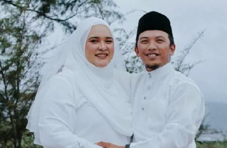 Norfarha Alia Mohd Sukri with her husband Muhammad Syazreen Wahid on their wedding day. They are wearing white and are smiling widely.