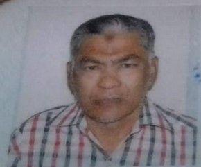 Zeawdeen Kadar Masdan in a passport photo wears a checquered shirt. He has brown skin and salt and pepper hair and goatee.