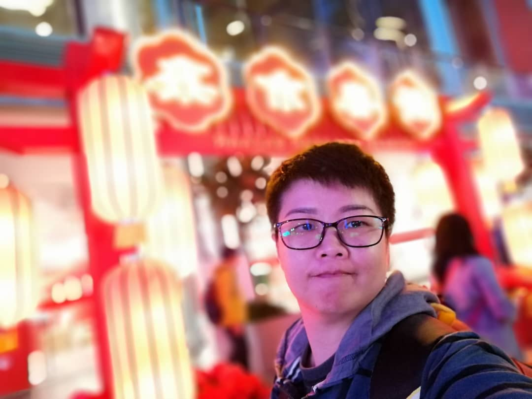 Cheng Pei See poses in front of Chinese lanterns. She has short hair, a round youthful face and dark-rimmed spectacles.