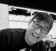 Moan Wai Meng smiles widely as he leans into a shot for the camera. He has floppy hair and dark-rimmed glasses.