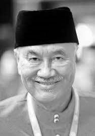 Rizuan Abd Hamid, an elderly man with a greying mustache and lines on his face, wearing a songkok and baju melayu, while smiling to the camera.