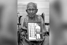 Ujang Mormin, 100 - an old man with thinning, white hair, lines on his face and glasses, sits on in a wheelchair while holding a framed portrait of himself in Royal Malay Regiment uniform of while baju melayu and sampin.