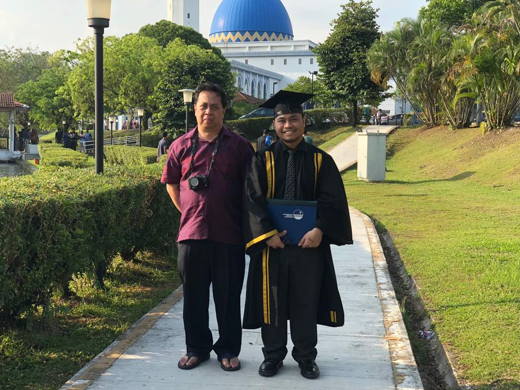 Razli Shawari stands next to his son Fikhri, who is in a graduation gown. Razli has a camera around his neck.