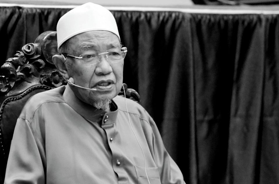Harussani Zakaria. An elderly man in a kopiah and baju melayu. He has grey, bushy eye brows and a grey goatee. He is sat on a chair with elaborate carvings and is speaking into a microphone attached to his face.