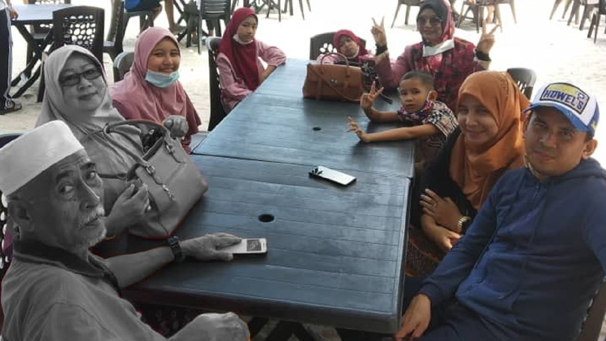 Zurina Othman and Che Embi Mat sit at a restaurant table with their family.