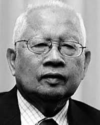 Tun Mohamed Salleh Abas, 91. An elderly man with white thinning hair, thinning eyebrows and a broad nose.He is pictured wearing glasses, a checquered shirt buttoned up to the collar and a jacket.