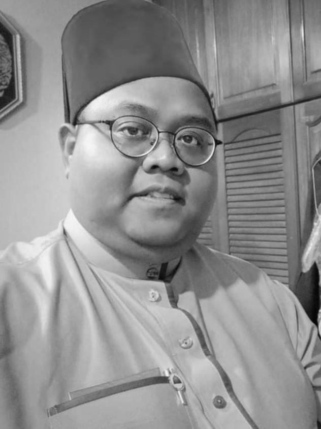 Muhammad Nazirul Jamaludin, 32 - a rotund young man in a tarbush, round-framed glasses and high collared shirt, standing in front of a cupboard.