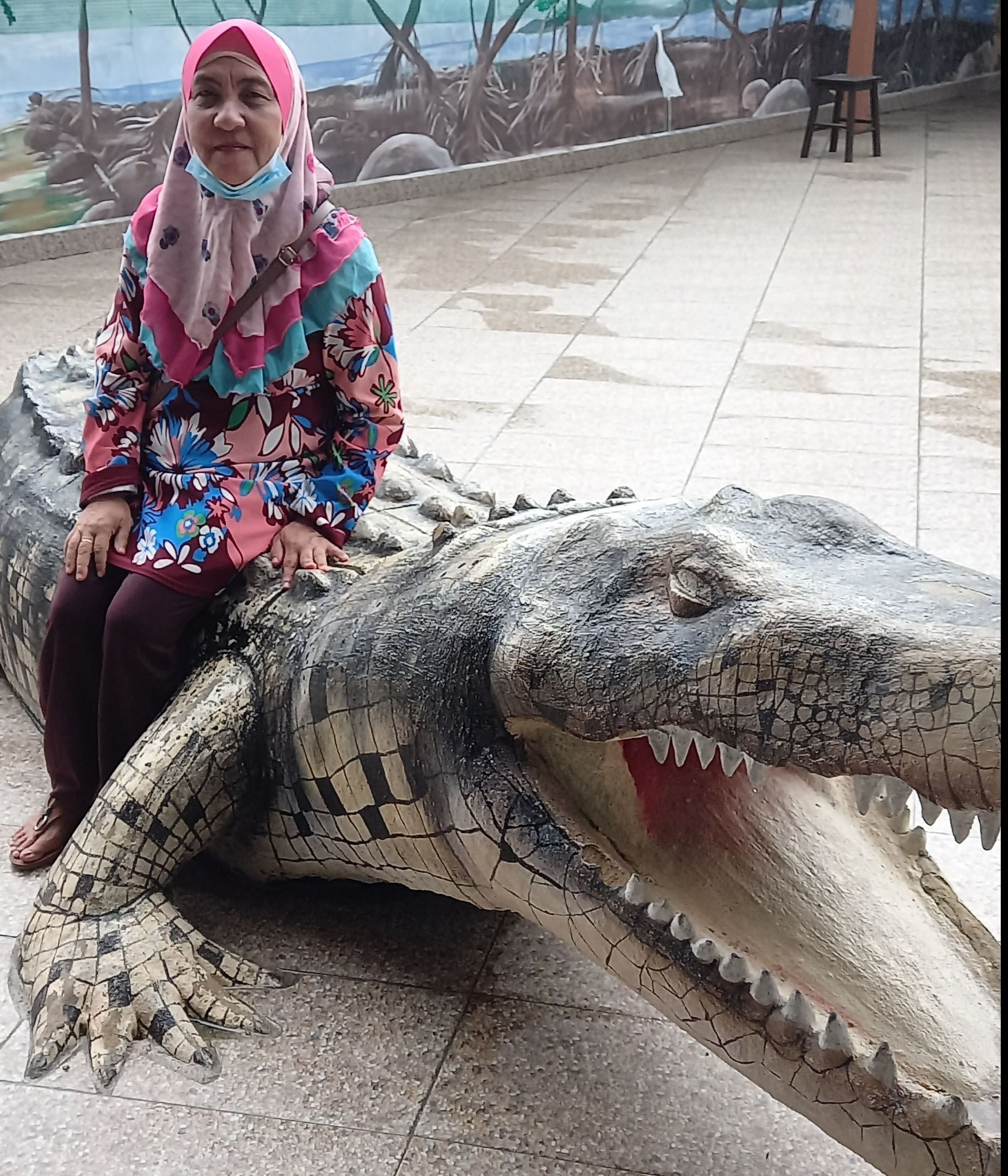 Zaiton Binti Ahmad poses on a replica crocodile. She is wearing a ruffled headscarf and a floral blouse. She is smiling.