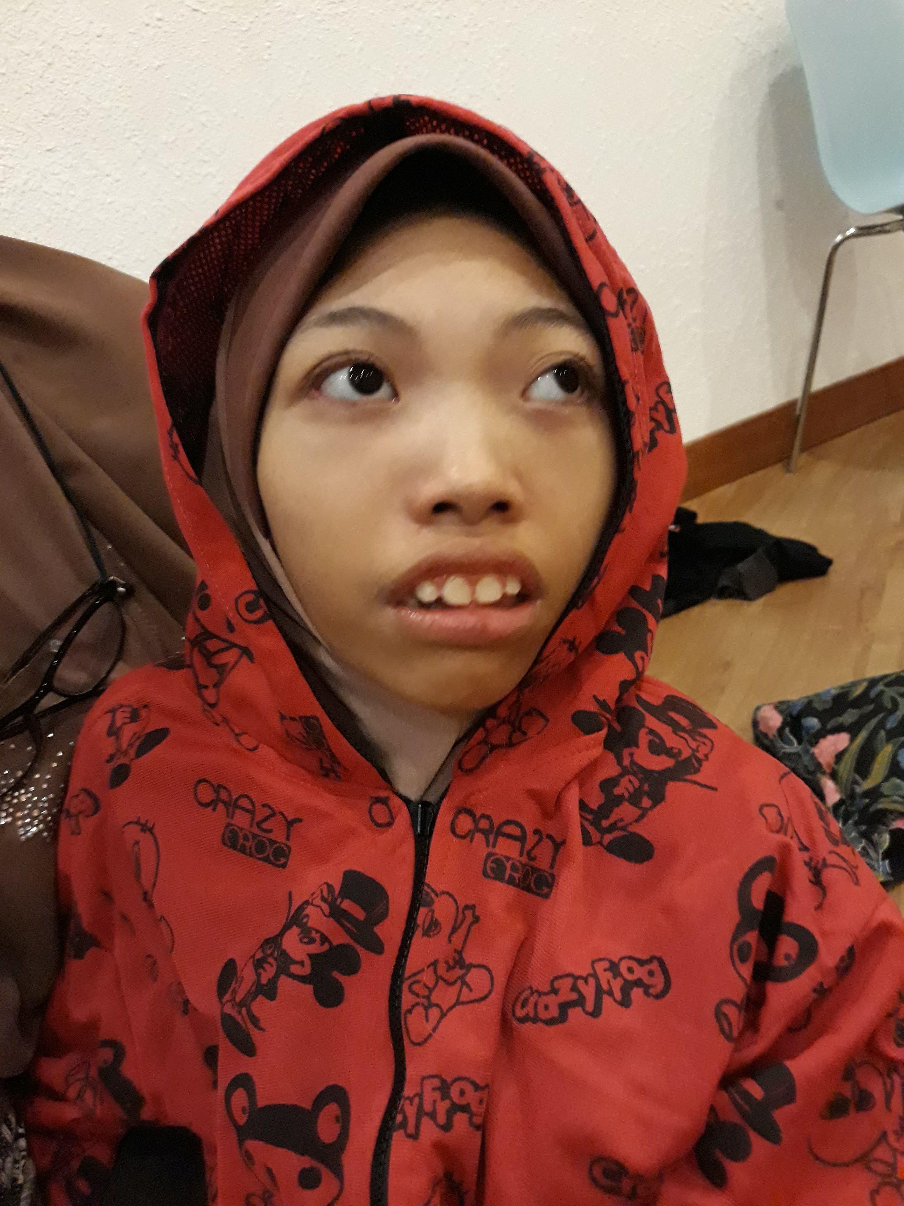 Nurul Ain Binti Shaari memakai jaket yang mempunyai hud, berwarna merah dan bergambar kartun Mickey Mouse.