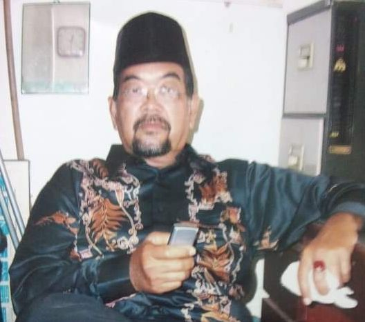 Said sitting on a chair wearing a beautiful green batik and black songkok
