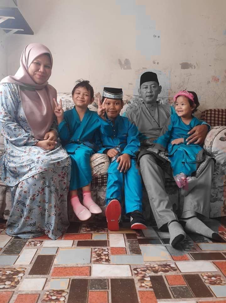 Abdul Razak Jemali poses with his wife and three children on Hari Raya Aidilfitri 2021. He has a young daughter on his lap. They are wearing festive clothes.