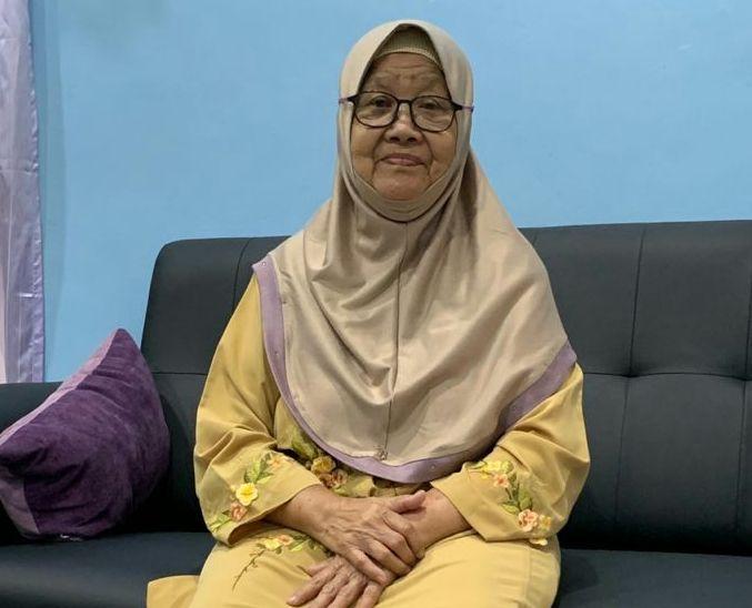Jusmah Binti Ahmad posing at home during Hari Raya celebration. She wears glasses, a plain headscarft and floral baju kurung.