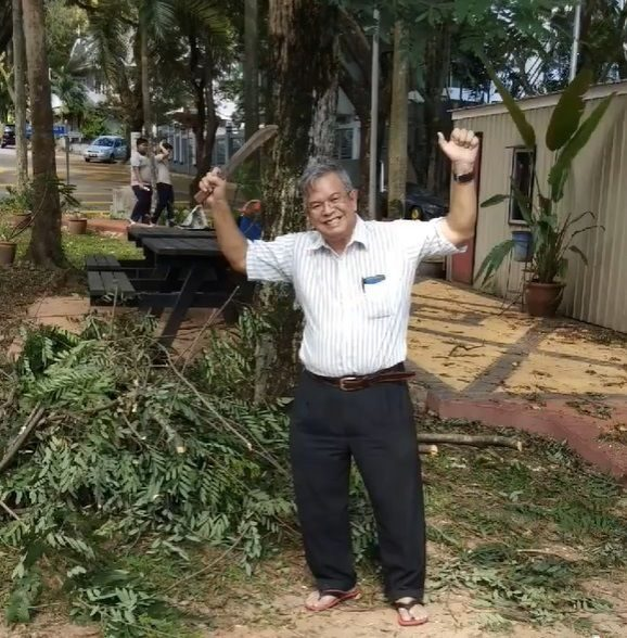 Che Jumaat celebrating after using a parang to hack down a tree in his neighbourhood.