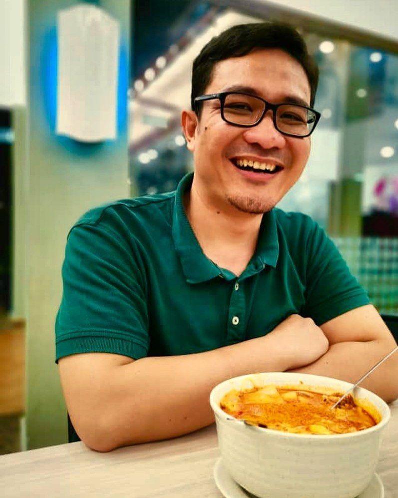 Khairil Azhar memakai cermin mata, tersenyum lebar menampakkan gigi