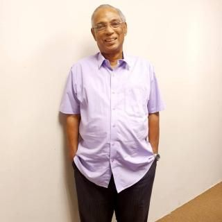 Dr Anthonysamy Savarinathan. An elderly man with thinning grey hair and rimless glasses, stands smiling with his hands in his trouser pockets. He is wearing a short-sleeved button down shirt.