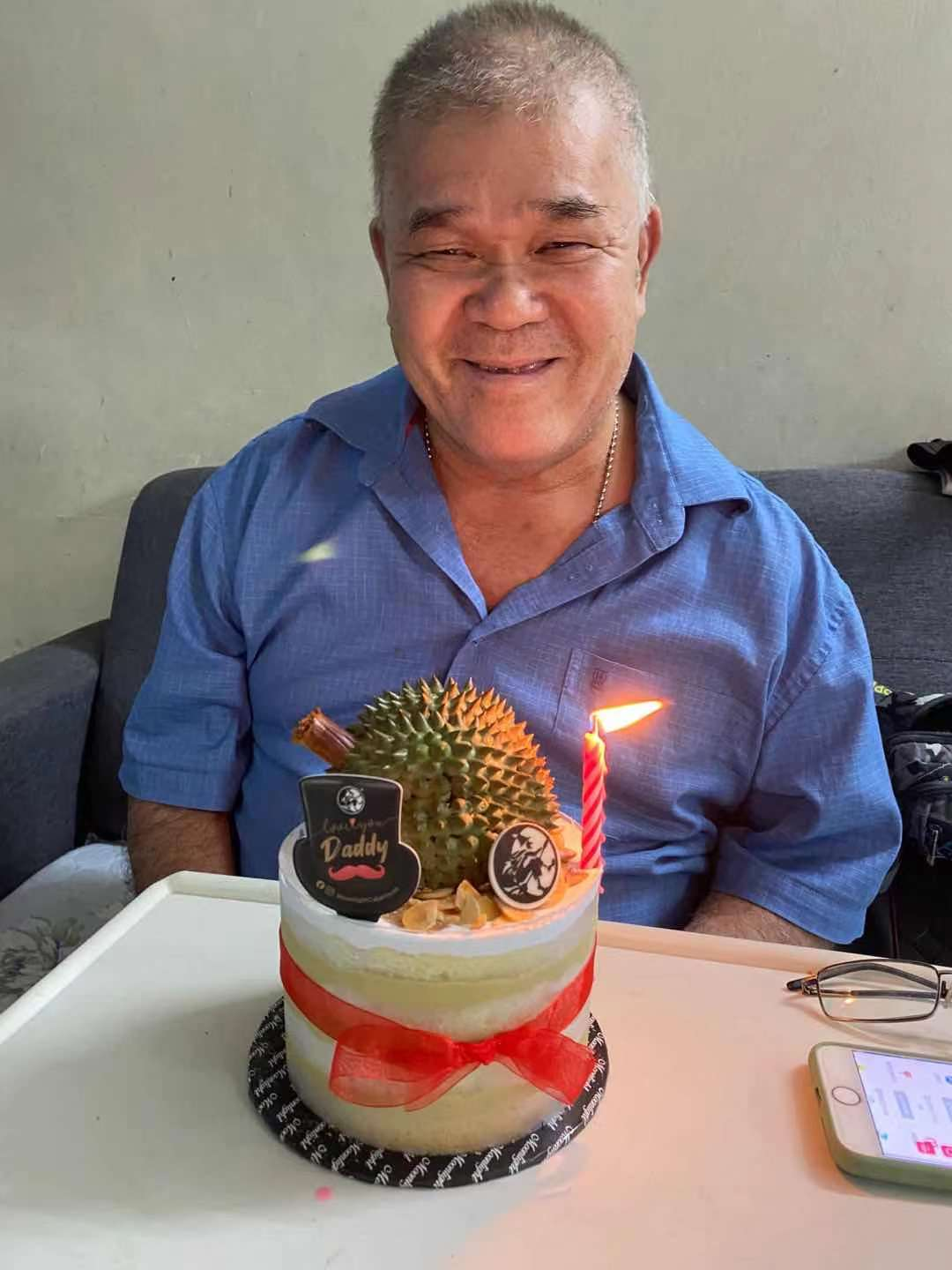 Ng King Hu, smiles in front of a cake which has a single lit candle, a durian replica and the words 'Daddy'.