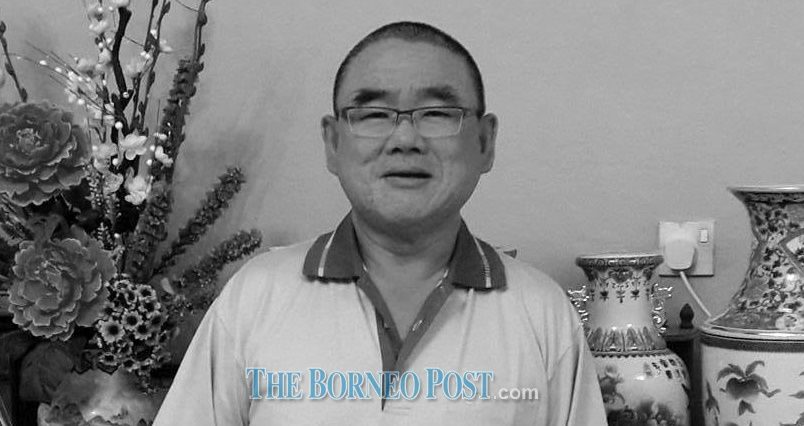 Yeo Kian Leong, 61, has short cropped hair, wears glasses and a collared T-shirt. He is standing in front of some vases and artificial flowers.