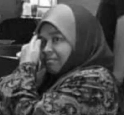 Nazita Idris, 45. Middle-aged, rotund woman in headscarf and patterned baju kurung.